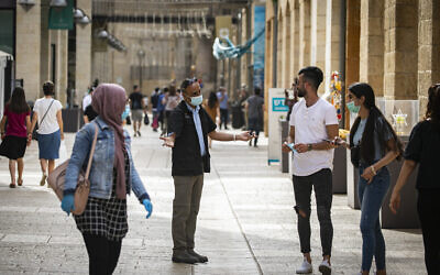 A security guard asks people to put on face masks at the Mamilla Mall near Jerusalem's Old City on May 14, 2020. (Olivier Fitoussi/Flash90)