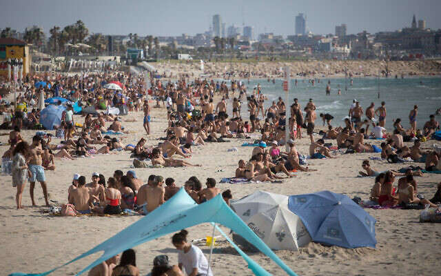Defying COVID-19 restrictions, Israelis enjoyed the beach in Tel Aviv, as temperatures rose to 40 degrees in some parts of the country, May 16, 2020. (Miriam Alster/Flash90)