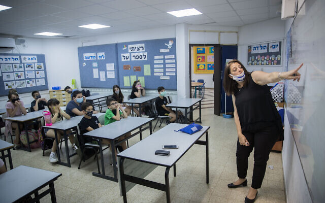 Israeli students and teachers wear protective face masks as they retun to school, at Hashalom School in Mevaseret Zion, near Jerusalem, May 17, 2020 (Yonatan Sindel/Flash90)