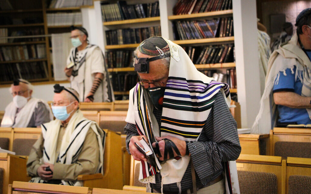 Illustrative: Jewish men pray at a synagogue in the West Bank settlement of Efrat, Gush Etzion, May 20, 2020. (Gershon Elinson/Flash90)