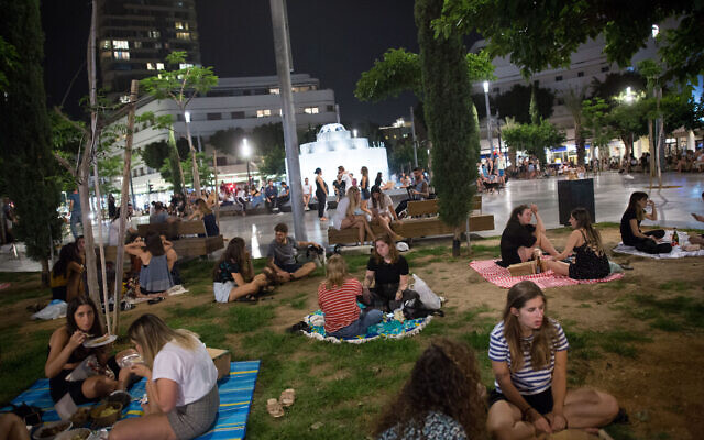 Israelis have picnics on Dizengoff square in Tel Aviv, as all restaurants, cafes and bars are still closed, except for take out and deliveries, in order to prevent the spread of the coronavirus. May 20, 2020. (Miriam Alster/Flash90)