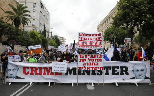 Members of the 'Black Flag' movement protest outside the Prime Minister's residence in Jerusalem, as Prime Minister Benjamin Netanyahu goes on trial for criminal allegations of bribery, fraud and breach of trust, May 24, 2020 (Olivier Fitoussi/FLASH90)