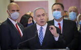 Prime Minister Benjamin Netanyahu (C), surrounded by Likud lawmakers, gives a televised statement before the start of his corruption trial at the Jerusalem District Court on May 24, 2020. (Yonatan Sindel/Flash90)