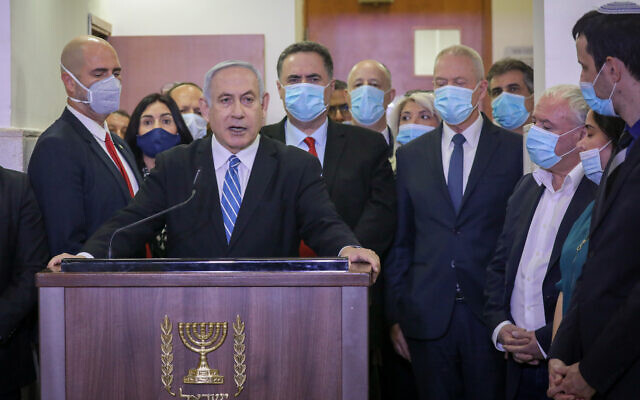 Prime Minister Benjamin Netanyahu, surrounded by Likud lawmakers, gives a televised statement before the start of his corruption trial at the Jerusalem District Court on May 24, 2020. Among the Likud ministers pictured (from left) are Amir Ohana, Miri Regev, Israel Katz, Tzachi Hangebi, Yoav Gallant, Eli Cohen and David Amsalem. (Yonatan Sindel/Flash90)
