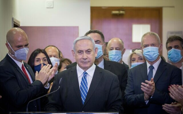Prime Minister Benjamin Netanyahu is surrounded by Likud lawmakers as he gives a press statement ahead of the start of his trial at the Jerusalem District Court, May 24, 2020 (Yonatan Sindel/Flash90)