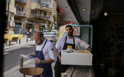 Chefs receives fresh fish as they prepare to reopen the Yudale tapas bar in Jerusalem, on May 25, 2020. (Olivier Fitoussi/Flash90)