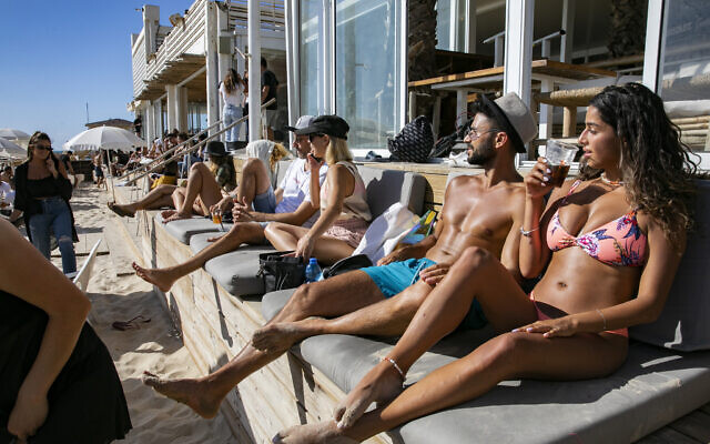 Israelis lounge outside a closed restaurant on the beach in Tel Aviv, on May 25, 2020 as the beaches of Tel Aviv were officially re-opened for the public after they were closed in order to prevent the spread of the coronavirus. (Olivier Fitoussi/Flash90)
