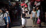 Some people wear protective face masks, while some don't, as they shop at the Carmel market in Tel Aviv, on May 26, 2020 (Miriam Alster/FLASH90)