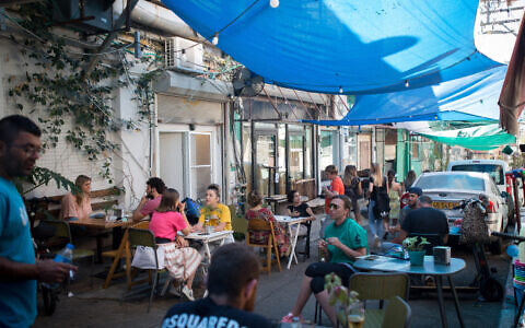 People sitting at a restaurant at the Carmel market in Tel Aviv on May 26, 2020. (Miriam Alster/FLASH90)