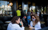 Customers at a cafe in Tel Aviv after they were allowed to reopen, following a closure of several weeks due to the coronavirus. May 27, 2020. (Miriam Alster/Flash90)