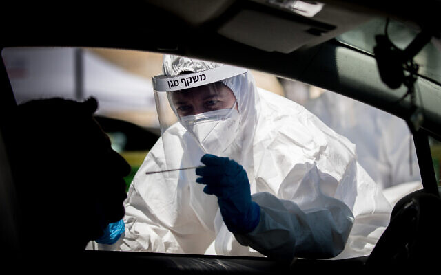 Magen David Adom medical workers perform coronavirus tests at a drive-through testing site in Jerusalem on May 30, 2020. (Yonatan Sindel/Flash90)