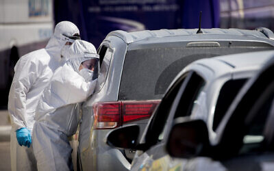 Magen David Adom medical workers at a drive-through site to collect samples for coronavirus testing in Jerusalem on May 30, 2020 (Yonatan Sindel/Flash90)