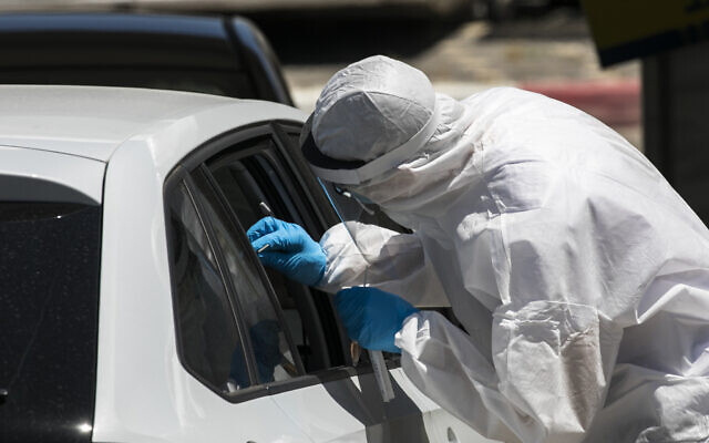 Magen David Adom medical workers test Israelis for the coronavirus at a drive-through site in Jerusalem on May 31, 2020. (Olivier Fitoussi/Flash90)