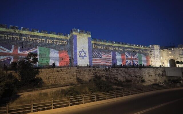 The flags of countries that are home to Jewish communities hard hit by COVID-19 projected on to the walls of the Old City of Jerusalem in a show of support sponsored by the Diaspora Affairs Ministry on May 12, 2020. (Igor Parvarov via JTA)