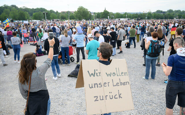 A protester carries a sign with the inscription 'We want our life back' during a demonstration in Stuttgart, Germany, against restrictions on social activity due to the coronavirus pandemic, May 9, 2020. (Sebastian Gollnow/picture alliance via Getty Images via JTA)