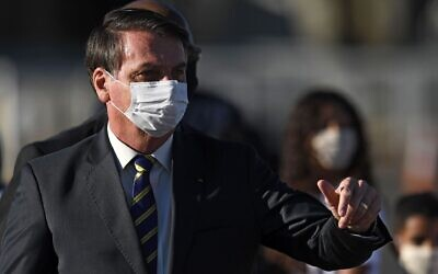 Brazilian President Jair Bolsonaro, wearing a face mask, gestures as he speaks to supporters while arriving at a ministerial meeting at the Alvorada Palace in Brasilia, Brazil, May 12, 2020. (Evaristo Sa/AFP via Getty Images)