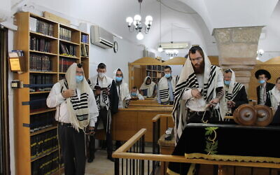 Men wearing masks pray in Jerusalem's Hurva Synagogue on May 21, 2020. (Sam Sokol)