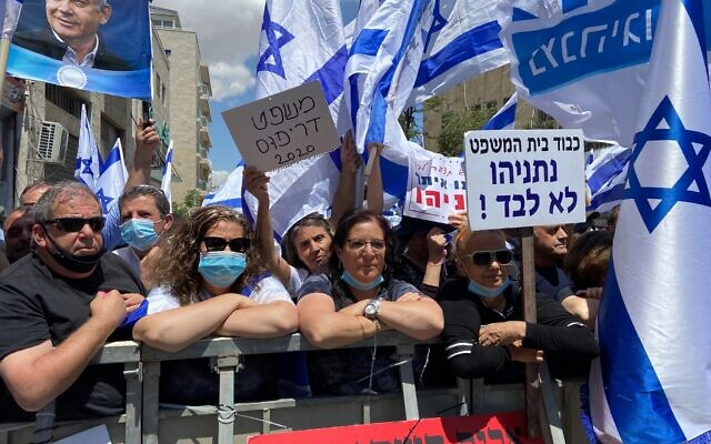 Police stand by as the hundreds of flag-waving pro-Netanyahu protesters pack up closely against one another in violation of social distance guidelines. (Jacob Magid/Times of Israel)