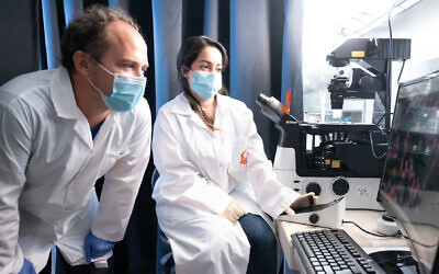 Ph.D student Esti Toledo and Postdoctoral fellow Guilaume Le Saux from the Department of Materials Engineering  photographed in Dr. Mark Schwartzman's lab. In collaboration with Prof. Angel Porgador's lab, they are developing nanomaterial coatings against viruses and bacteria, including coronavirus (Dani Machlis)