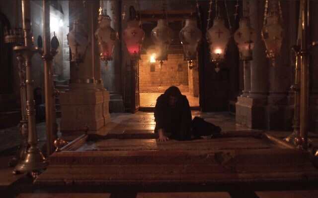 """Woman at the Stone of Unction in the Church of the Holy Sepulchre, as seen in 'Holy Fire"""" documentary film. (Cistern Films)"""