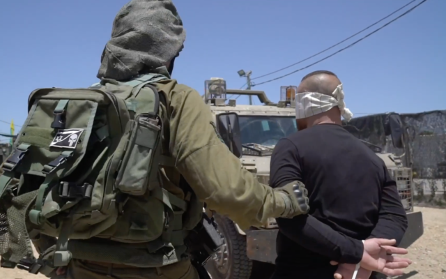An Israeli soldier arrests a Palestinian man as part of a manhunt for the person who threw a brick at Sgt. First Class Amit Ben-Ygal, killing him, in the West Bank village of Yabed on May 12, 2020. (Israel Defense Forces)
