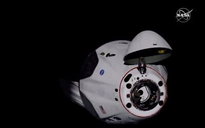 Screen capture from video of the SpaceX Dragon crew capsule, with NASA astronauts Doug Hurley and Robert Behnken aboard, as it docks with the International Space Station, May 31, 2020. (NASA TV via AP)