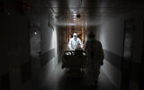 Medical workers move a coronavirus patient at an intensive care unit of the Filatov City Clinical Hospital in Moscow, Russia, May 15, 2020. (AP/Pavel Golovkin)
