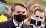 Brazil's President Jair Bolsonaro stands amid supporters taking pictures with cell phones as he leaves his official residence of Alvorada palace in Brasilia, Brazil, May 25, 2020. (AP/Eraldo Peres)
