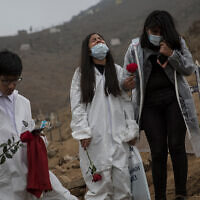 Children bury their father, who died from COVID-19 complications, at the Nueva Esperanza cemetery on the outskirts of Lima, Peru, May 28, 2020. (AP/Rodrigo Abd)