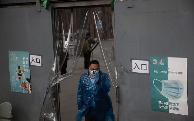 A worker stands near a processing station for passengers arriving from Wuhan in Beijing, April 19, 2020. (AP/Ng Han Guan)