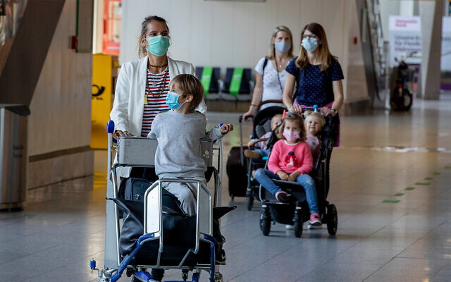 Wives and children of German business people working in China walk through a terminal at the airport in Frankfurt, Germany, May 29, 2020. (AP/Michael Probst)