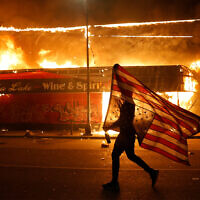 A protester carries a US flag upside down, a sign of distress, next to a burning building in Minneapolis, Minnesota following the death of George Floyd, May 28, 2020. (AP/Julio Cortez)
