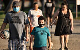 People wearing masks exercise around a track  in Los Angeles, May 9, 2020. (AP/Richard Vogel)