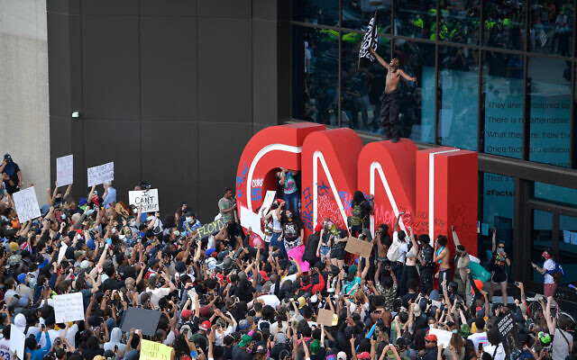 Demonstrators paint on the CNN logo during a protest march over George Floyd's death in Atlanta, Georgia, May 29, 2020. (AP/Mike Stewart)