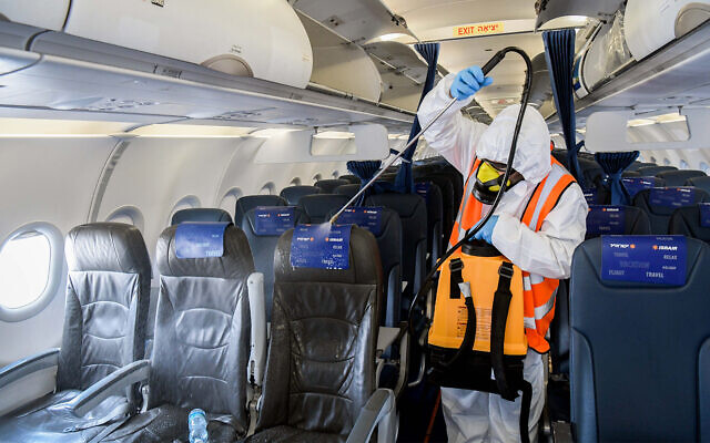 A worker disinfects a Israir plane at Ben-Gurion International Airport near Tel Aviv, May 5, 2020. (Yossi Zeliger/Flash90)