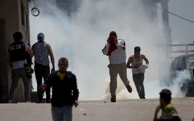 Palestinians run from tear gas fired by Israeli soldiers during clashes in the village of Yabad in the West Bank, May 12, 2020. (AP/Majdi Mohammed)