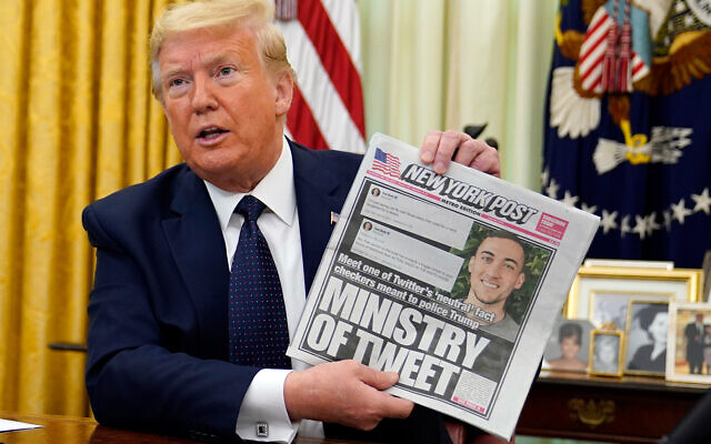 US President Donald Trump holds up a copy of the New York Post before signing an executive order aimed at curbing protections for social media giants, the White House, May 28, 2020. (AP/Evan Vucci)