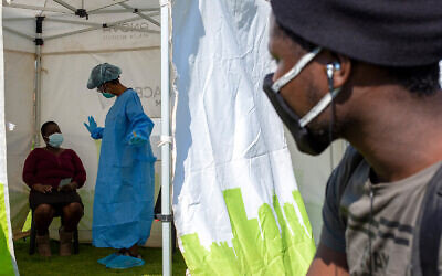 A man looks through a tent opening as a heath worker explains the process of collecting a sample for coronavirus testing near Johannesburg, South Africa, May 8, 2020. (AP/Themba Hadebe)