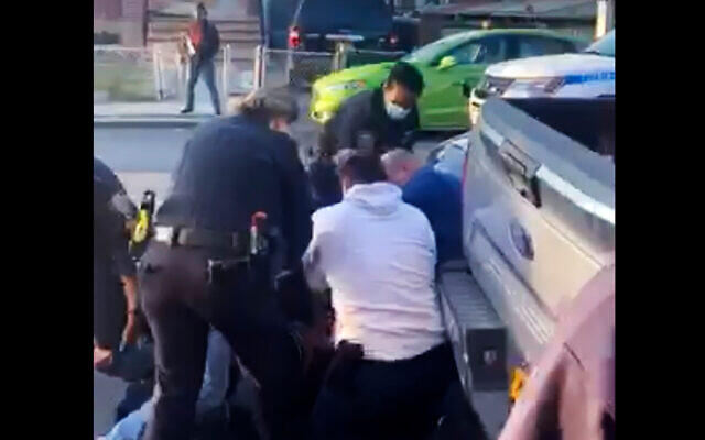 New York City police officers wrestle a man to the ground while making an arrest in the Brooklyn borough of New York, April 29, 2020. (Adegoke Atunbi via AP)
