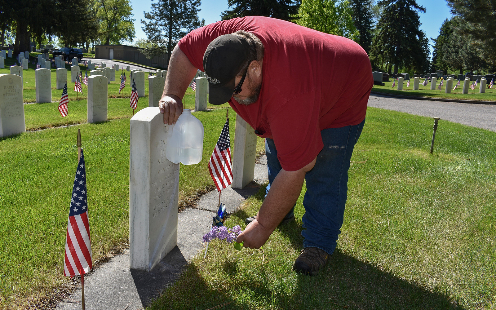 Frank Groblebe places lilacs at the grave of his parents, Frank and Helen Groblebe, at the Mountview Cemetery in Billings, Montana, May 25, 2020. (AP/Matthew Brown)