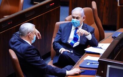 Blue and White chairman Benny Gantz (L) and Prime Minister Benjamin Netanyahu in the Knesset plenum on May 17, 2020, as their new coalition was sworn in. (Knesset)