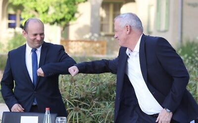 New Defense Minister Benny Gantz (R) and outgoing Defense Minister Naftali Bennett bump elbows at a passing of the baton ceremony at the Defense Ministry in Tel Aviv, May 18, 2020. (Oded Karni/GPO)