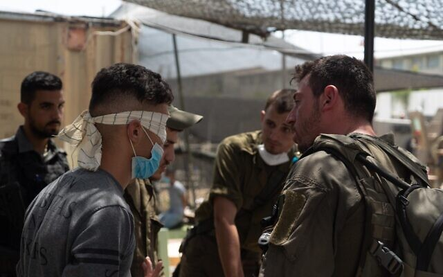 Israeli troops interrogate a Palestinian man as part of a manhunt for the person who threw a brick at Sgt. First Class Amit Ben-Ygal, killing him, in the West Bank village of Yabed on May 13, 2020. (Israel Defense Forces)