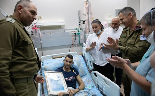 IDF Chief of Staff Aviv Kohavi, right, and Col. David Songo present an award to Staff Sgt. Shadi Ibrahim, center, who lost a leg after being hit by a car in a ramming attack in the West Bank, in Beersheba's Soroka Medical Center on May 27, 2020. (Israel Defense Forces)