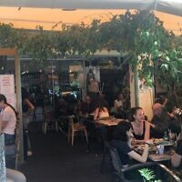 Young Tel Avivians at Cafe Zurik in Tel Aviv on the first day that restaurants were allowed to open after the coronavirus, May 27, 2020. (Simona Weinglass/Times of Israel)