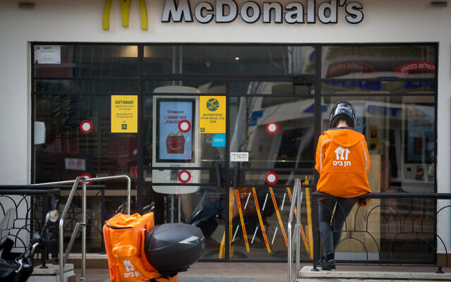 A food delivery man waits outside a McDonalds restaurant in Tel Aviv. April 18, 2020. (Miriam Alster/FLASH90) תן ביס