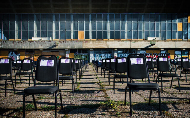 Chairs with fake money notes standing next to the decaying Palace of Concerts and Sports of Vilnius, Lithuania, on May 1, 2020. (Courtesy of the display's organizers, via JTA)