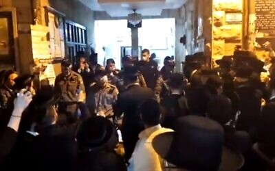 Dozens gather when police arrive to disperse a gathering in contravention of coronavirus regulations at synagogue in Jerusalem ultra-Orthodox neighborhood of Mea She'arim, May 15, 2020 (Screen grab/Kan)