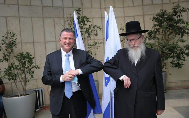 New Health Minister Yuli Edelstein (L) and outgoing Health Minister Yaakov Litzman at a passing of the baton ceremony at the Health Ministry on May 18, 2020. (Health Ministry)