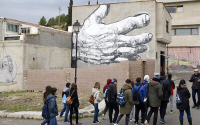 Students and their teacher walk past a street art mural on the facade of a house in Fanzara near Castellon de la Plana, on December 15, 2016. (JOSE JORDAN/AFP via Getty Images)